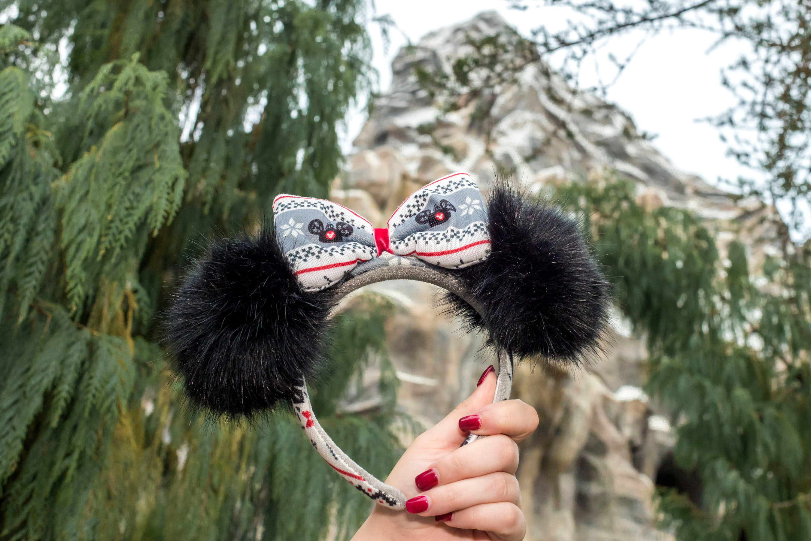 This pair of Minnie Mouse Sweater Pom Pom Ears featuring a knit bow is one of the three seasonal Minnie Ears designs found throughout Disneyland Resort in California and Walt Disney World Resort in Florida during the holiday season. (Joshua Sudock/Disneyland Resort)
