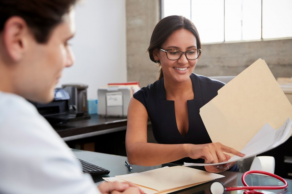 Young female doctor showing file to male patient at meeting